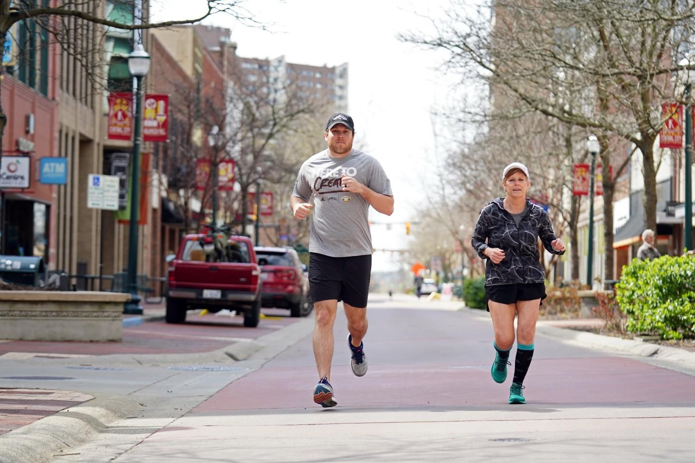 A man and woman running on the Kalamazoo Mall.