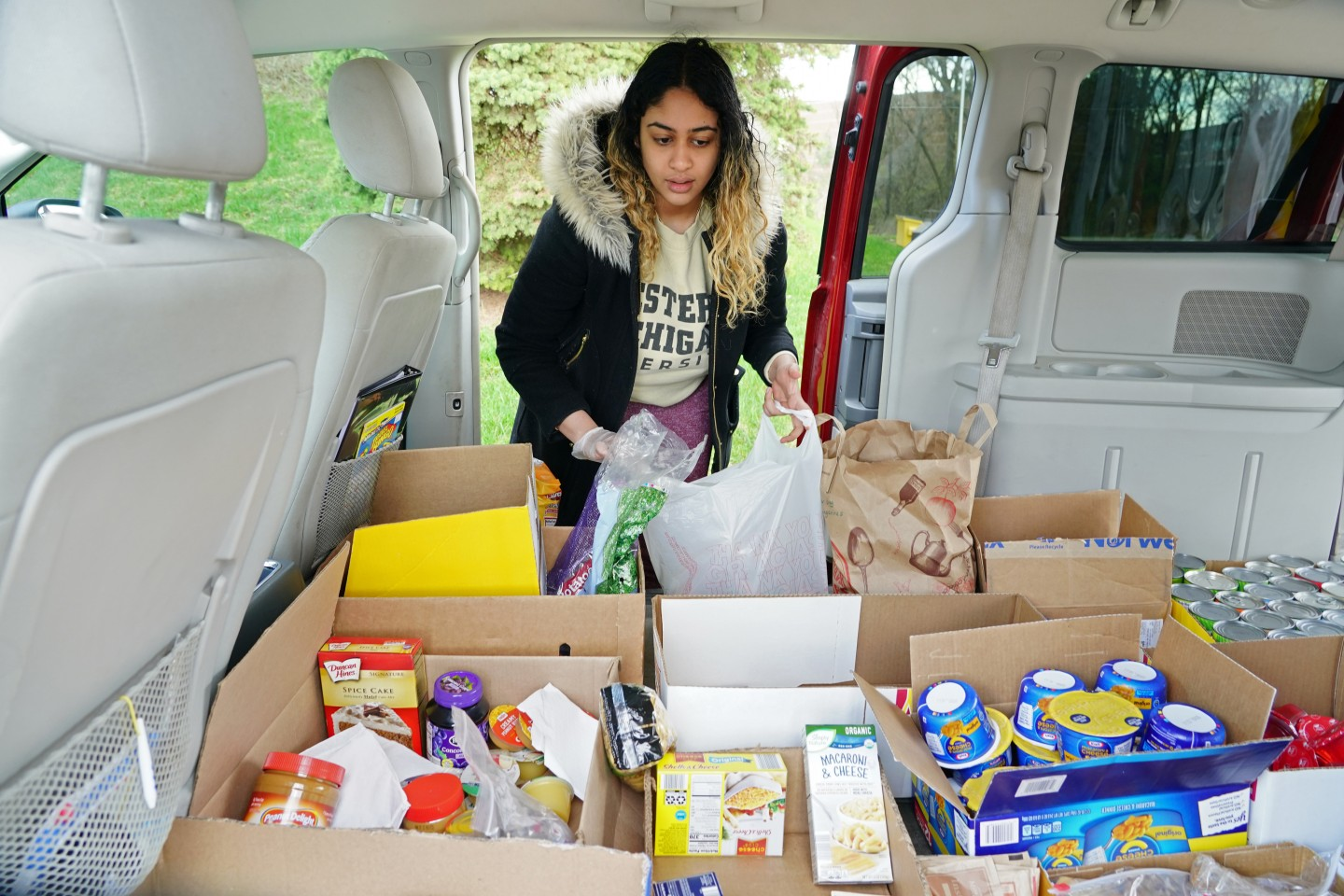 A student collects donated groceries from a van.