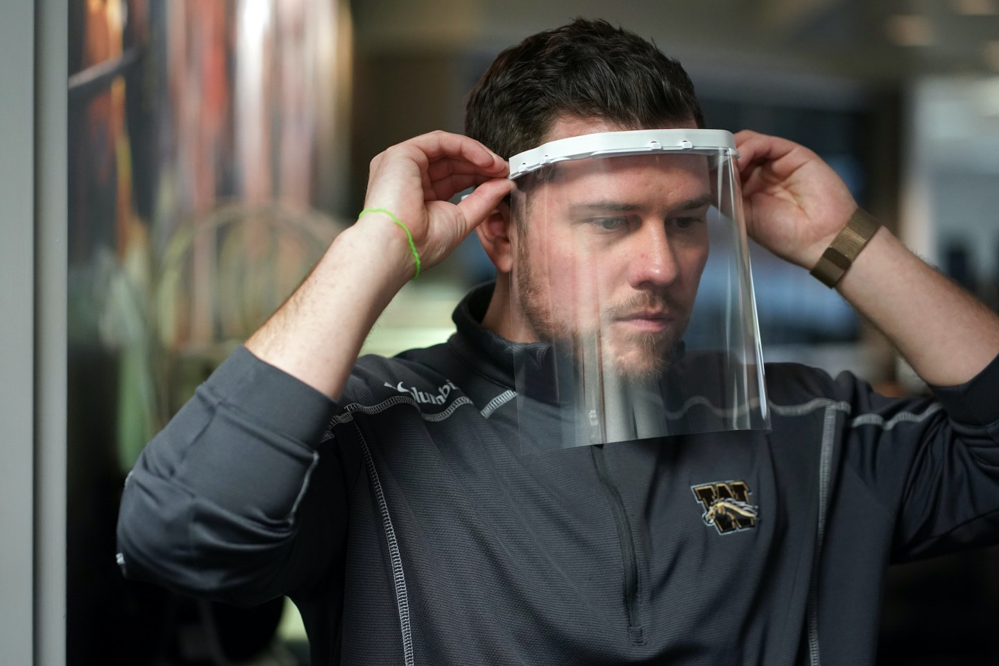A Western Michigan University worker models a face shield produced for healthcare workers.