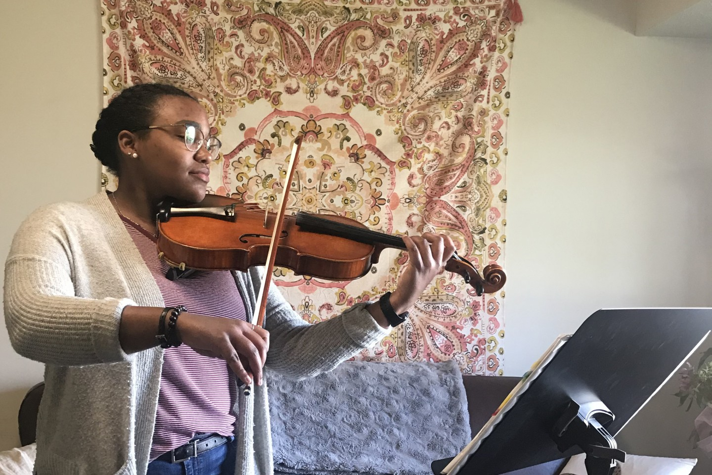 Kennedy Dixon plays viola in her apartment.