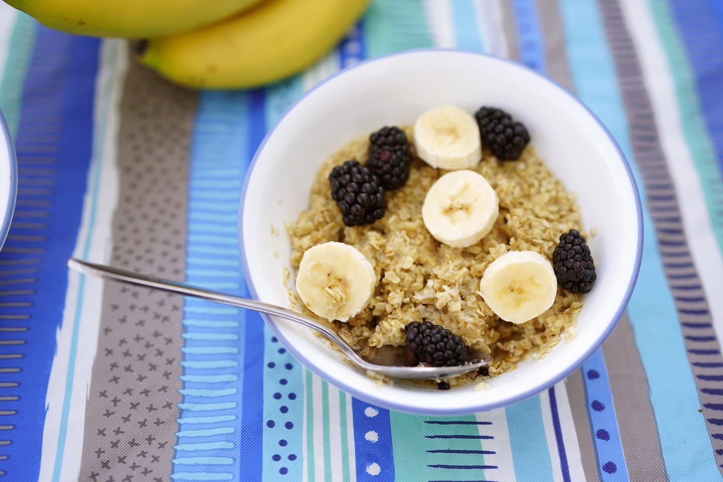 A bowl of oatmeal with bananas and blueberries.