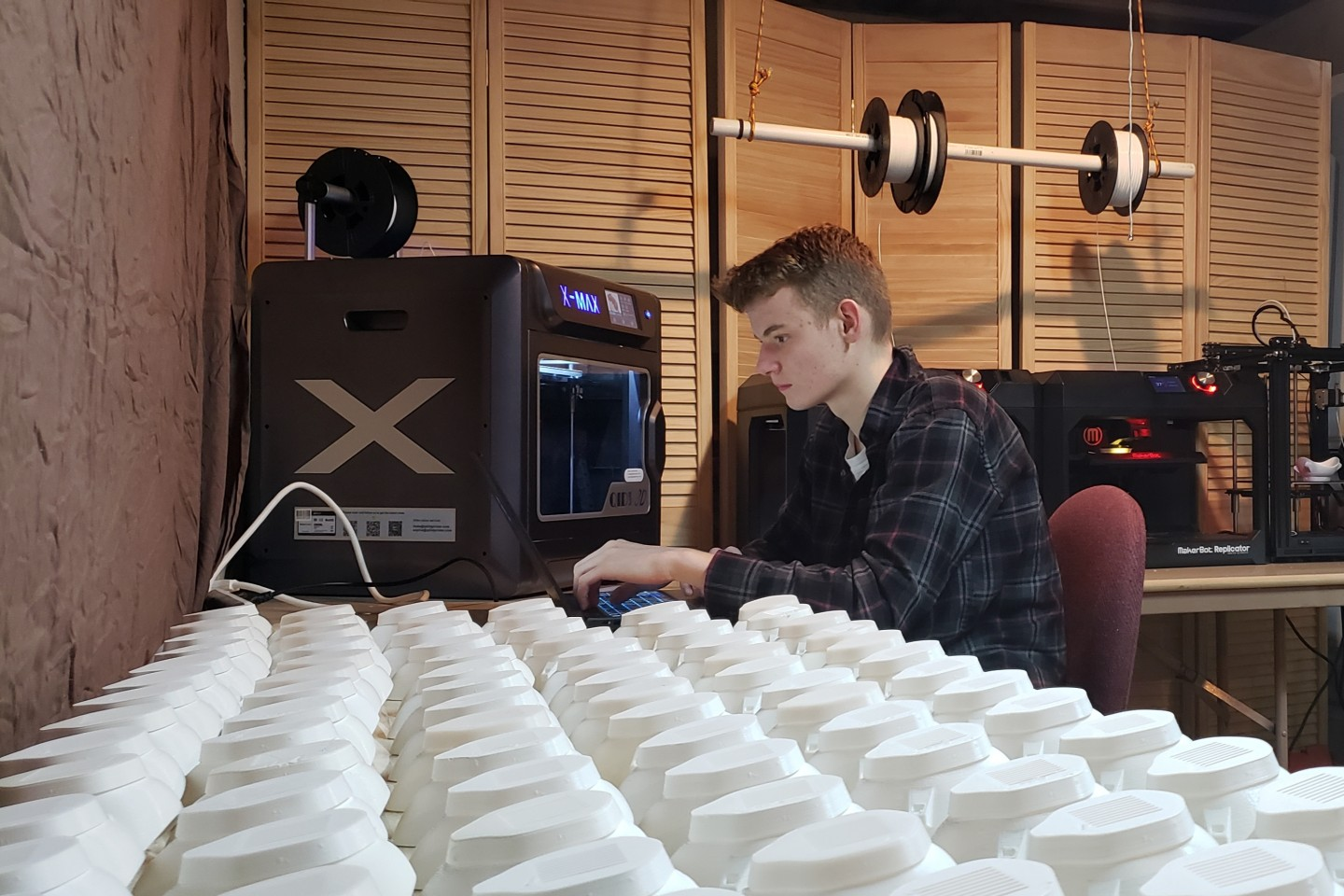 Ryan Barker sits at his 3D printer next to dozens of masks he's created.