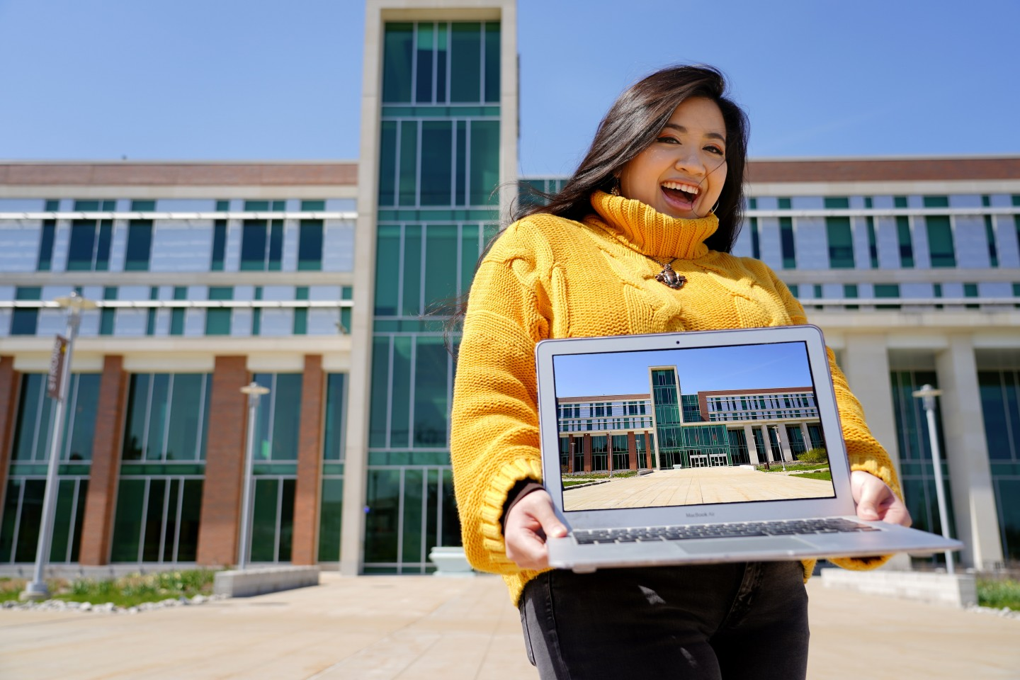A student ambassador holding a laptop while standing in front of Sangren Hall.