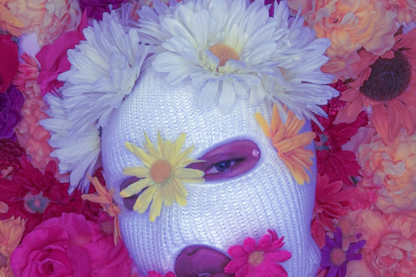 A woman wearing a face mask with flowers on the mask and surrounding her.
