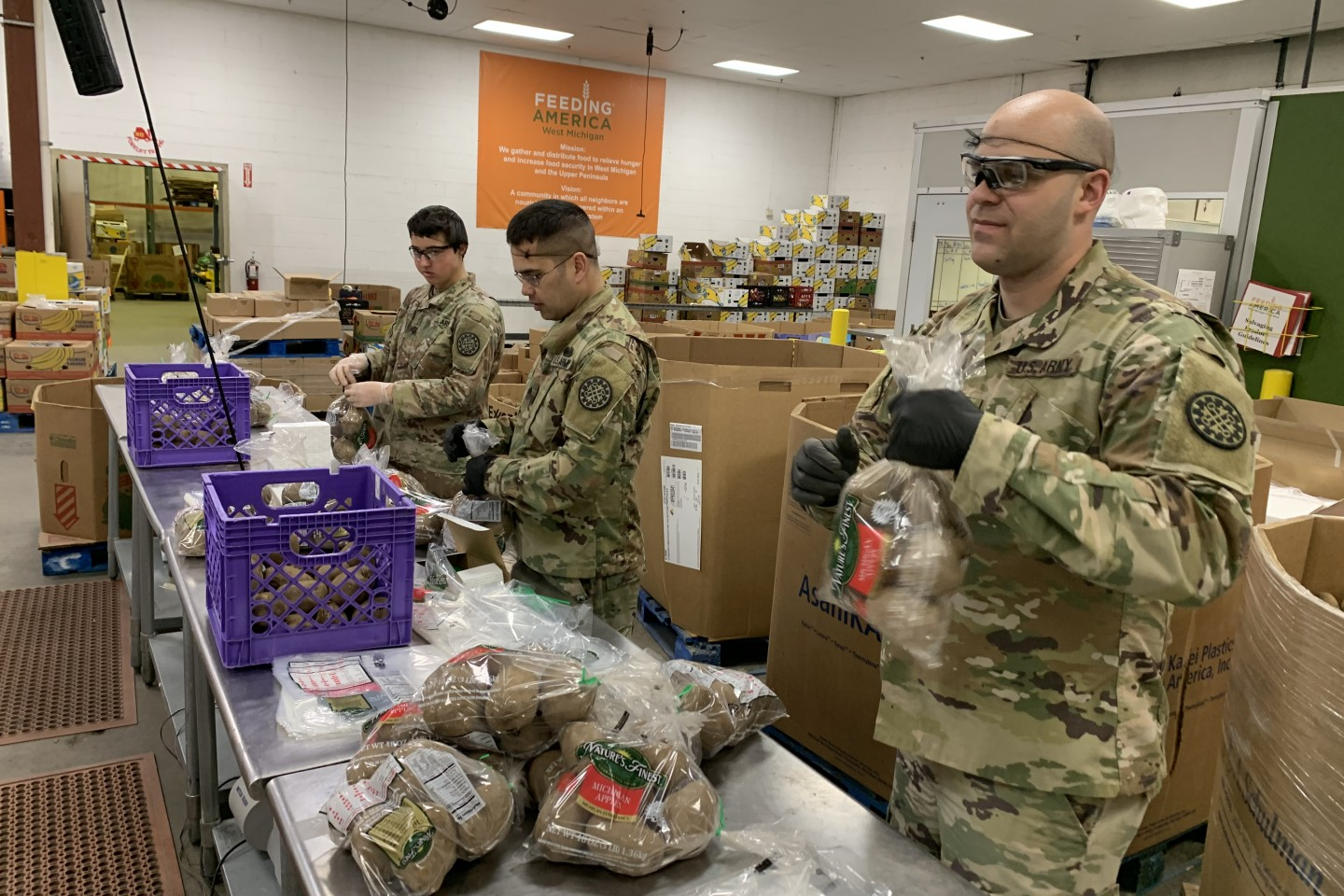 Soldiers pack boxes of food.