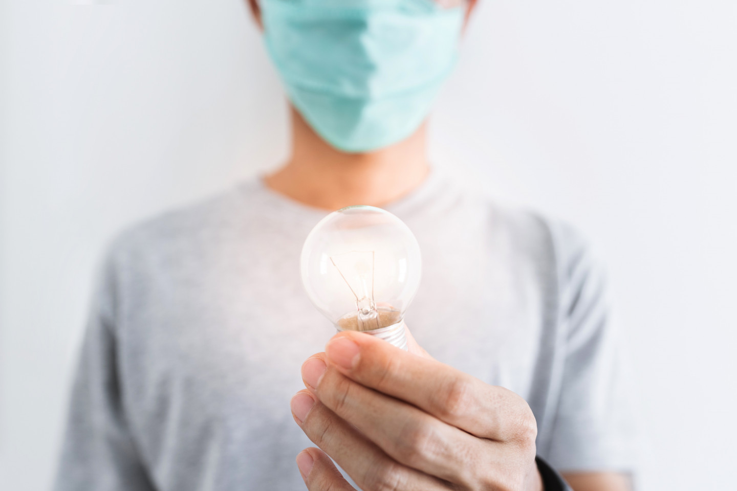 A person in a surgical mask holds a light bulb.