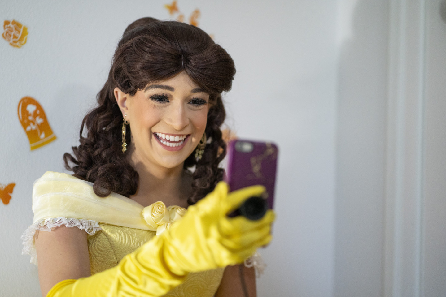 A student dressed as a princess smiles on a FaceTime call.