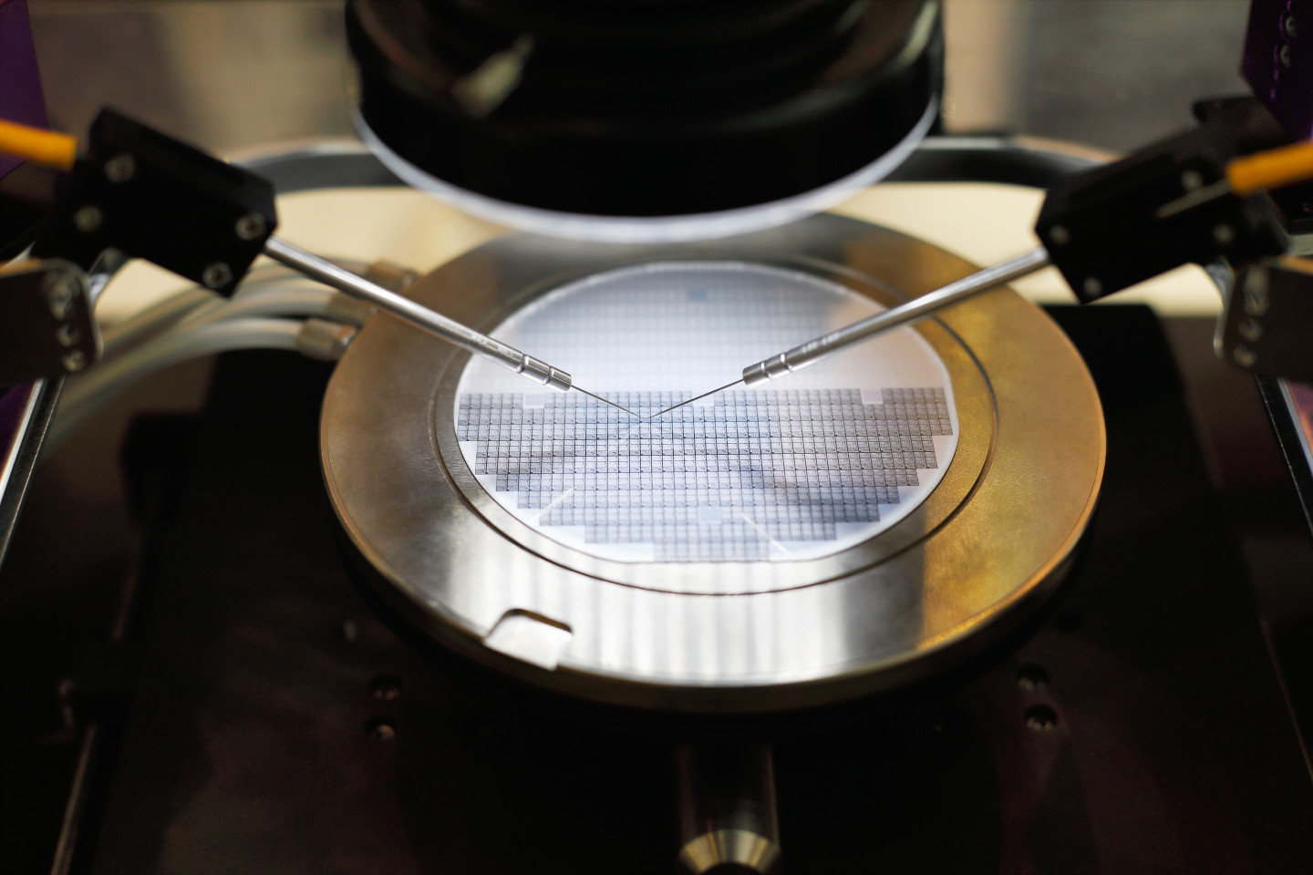 Two robotic arms working on a semiconductor wafer.