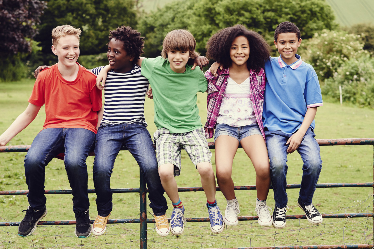 A group of kids sits on a fence.