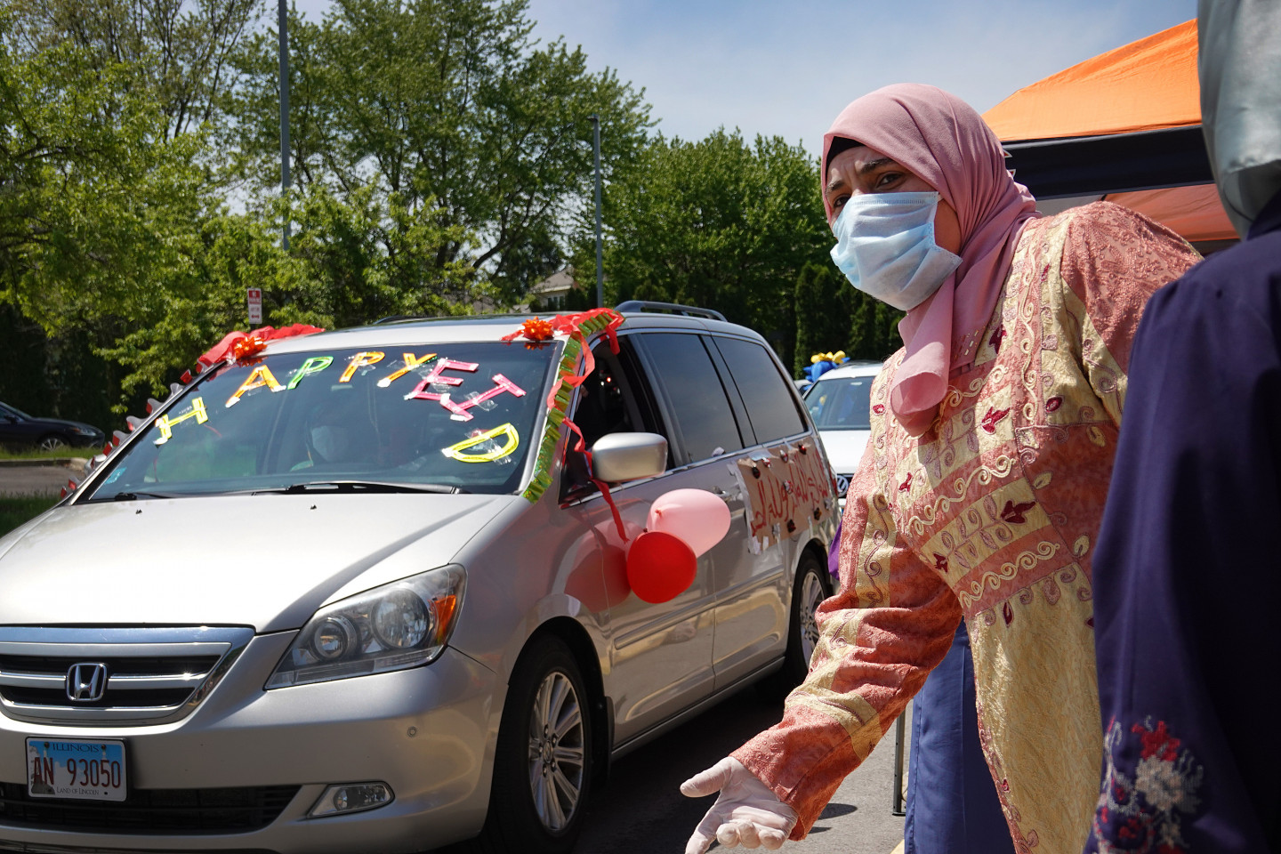 A woman wearing a mask stands next to a car decorated for Eid.