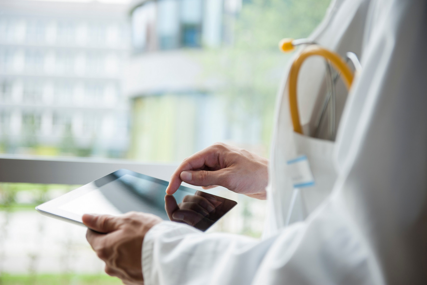 A doctor uses a tablet.
