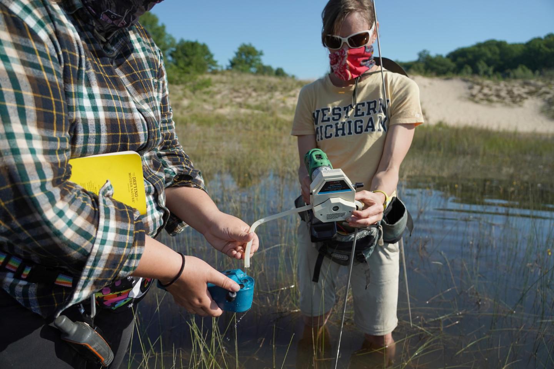 Dr. Tiffany Schriever uses equipment to analyze water in an interdunal wetland.