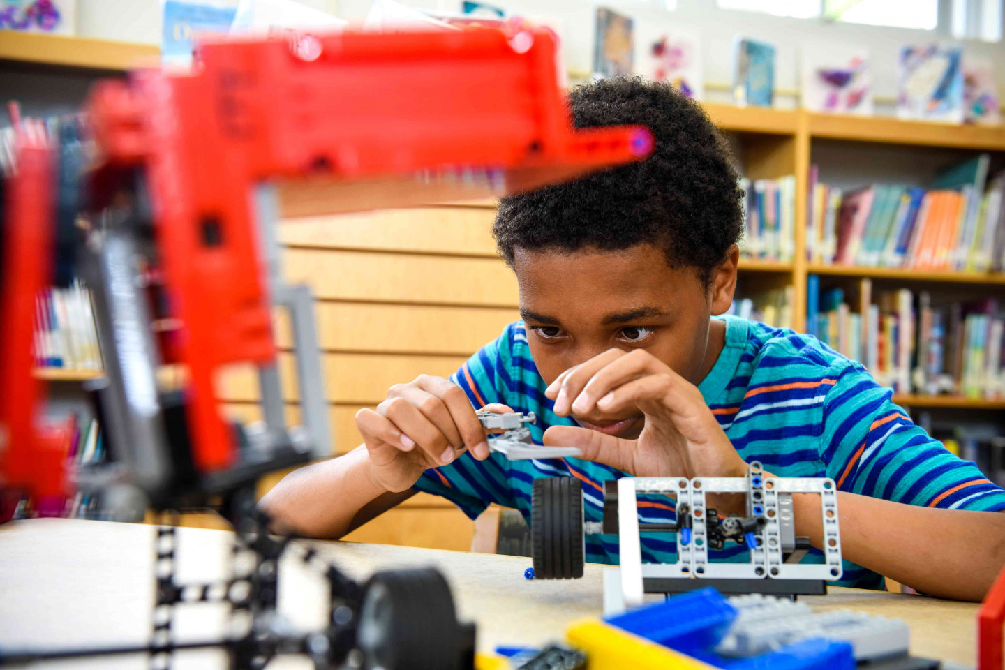 A child works on an engineering project in a classroom.