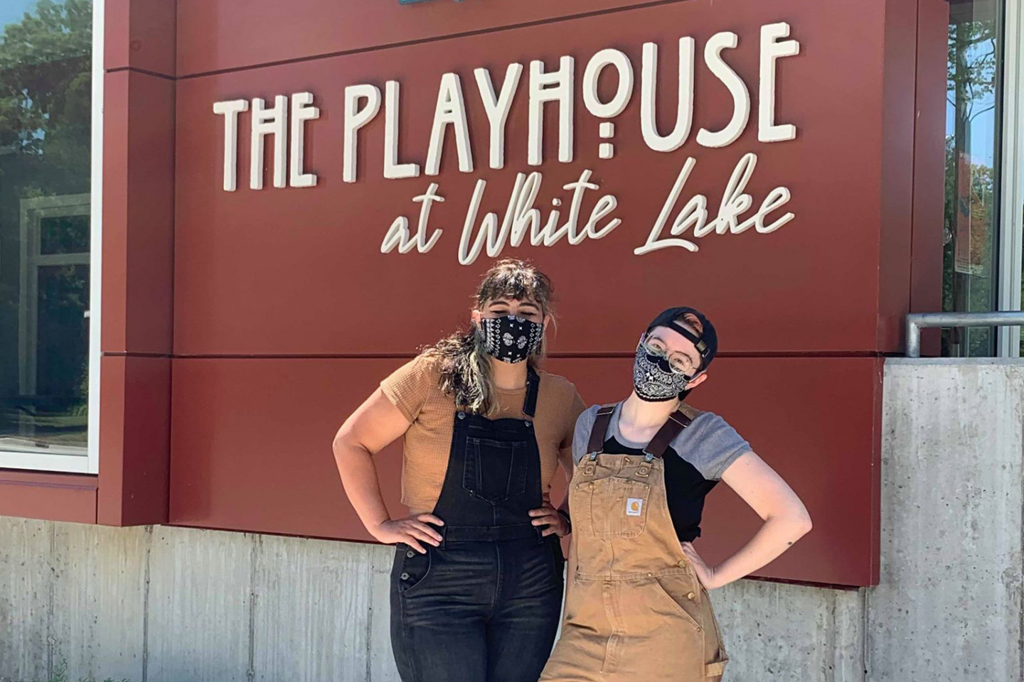 Caroline Arana and Claire Beaman stand together in front of the Playhouse at White Lake sign.