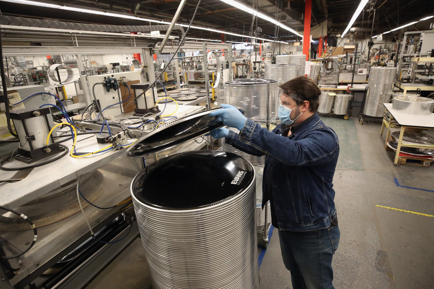 A worker assembles a product in a manufacturing facility.