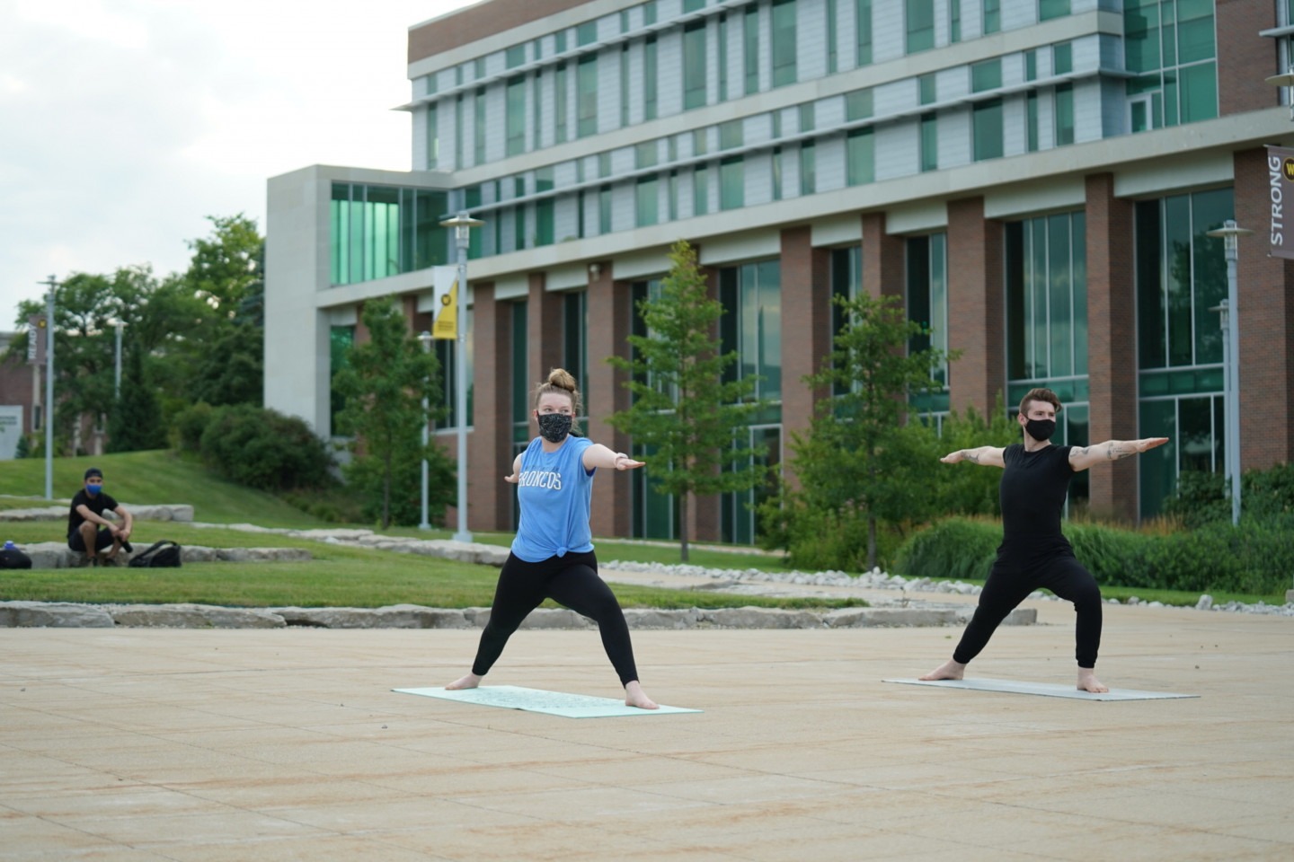 Students in masks practicing yoga on campus.