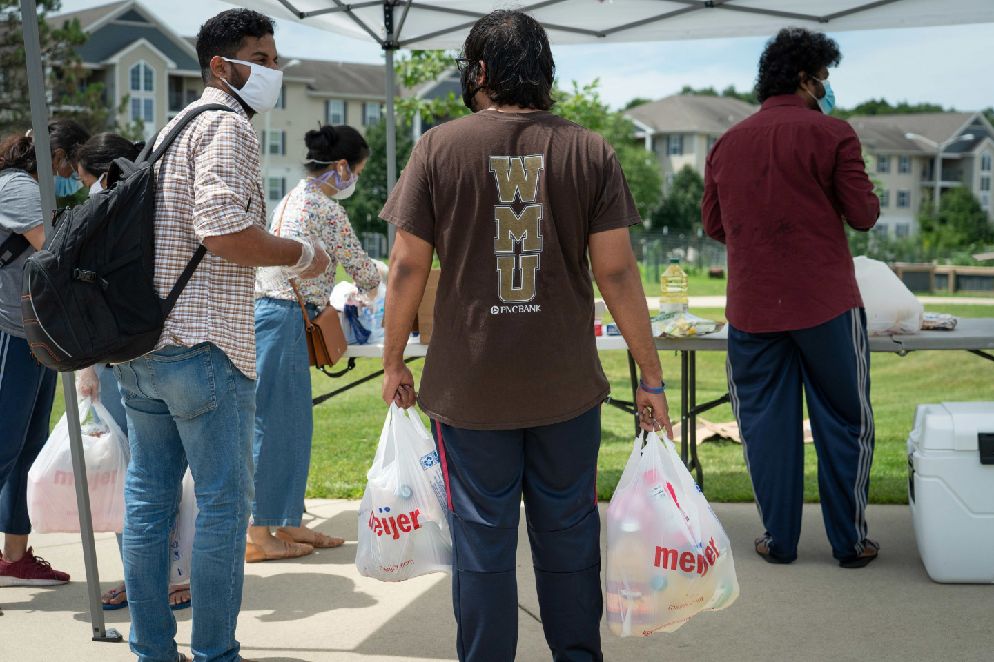 Students hold bags of free groceries.