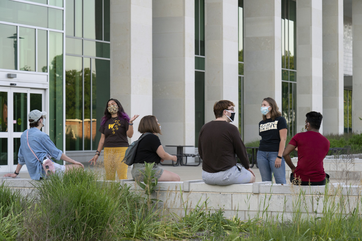 A group of students with masks sit and stand in front of Sangren Hall.