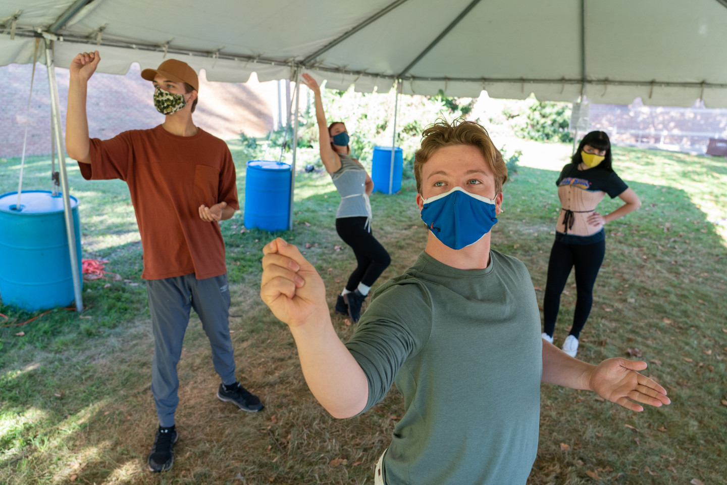 Student actors rehearse for an upcoming production outside under a tent.