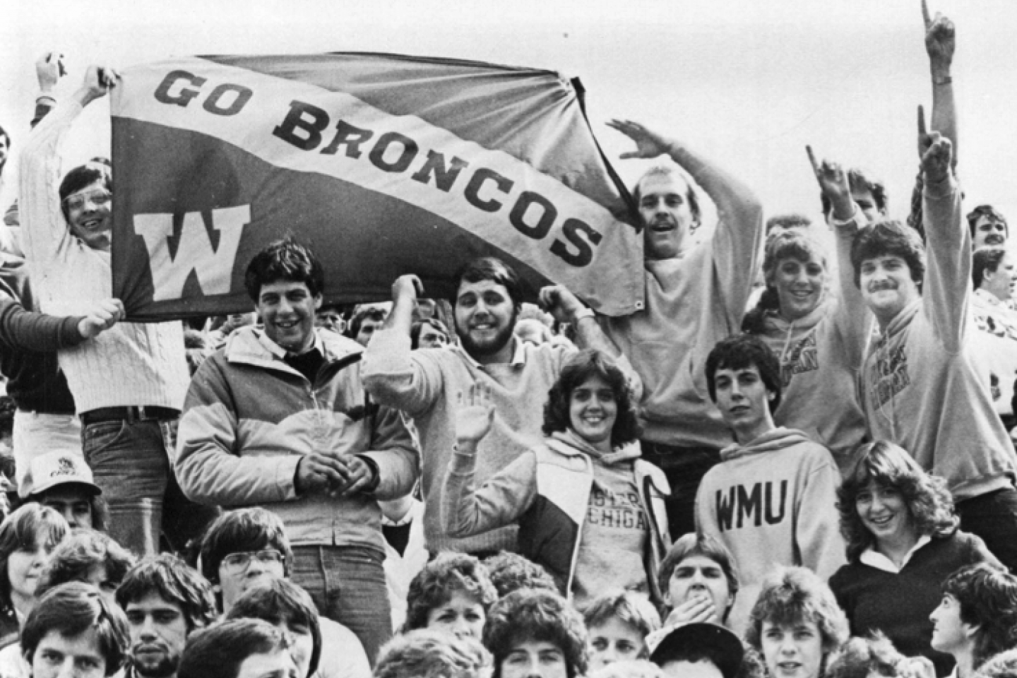 """Bronco fans holding up a flag that says """"Go Broncos"""" in 1982."""