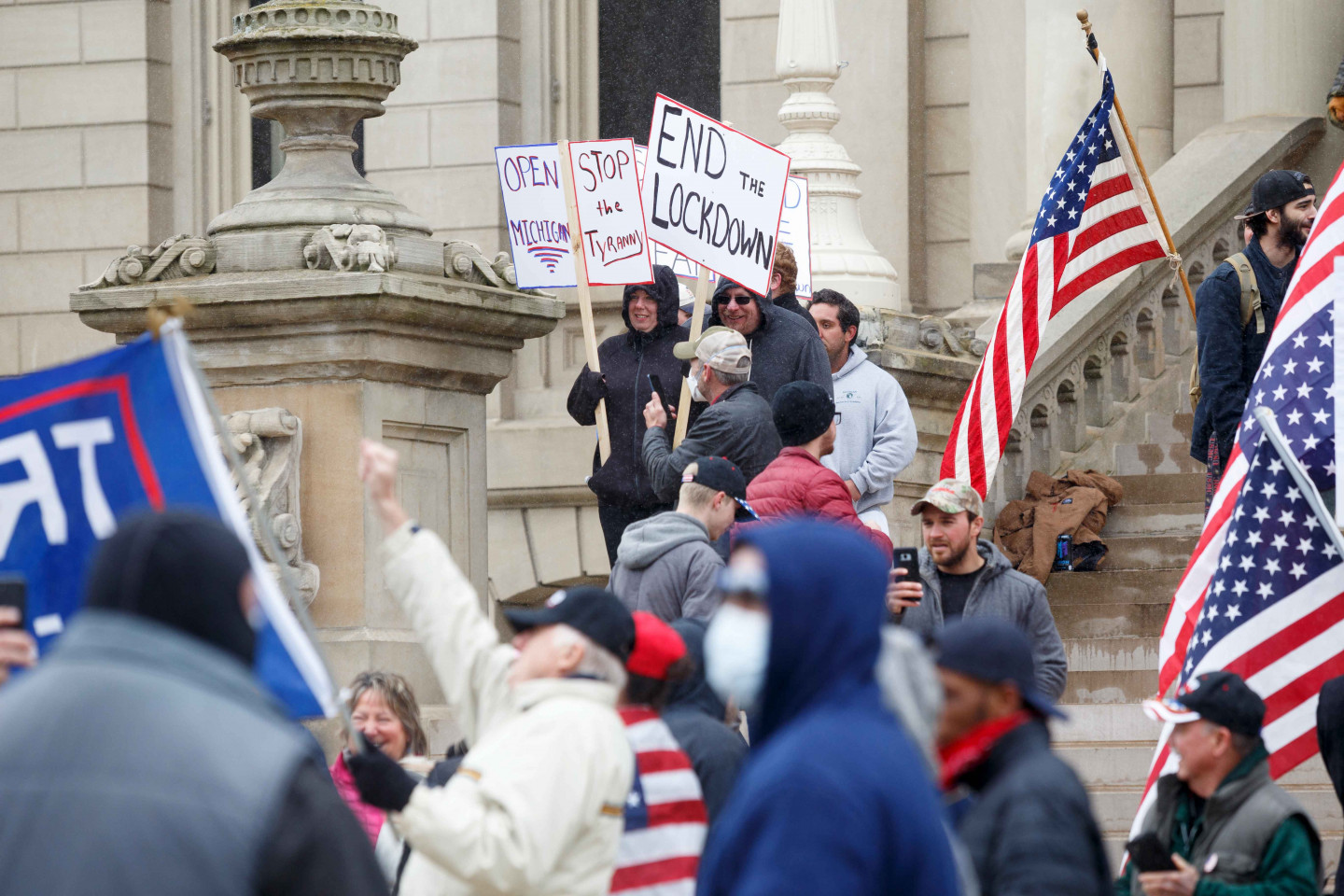 People demonstrate with flags and signs on the steps of the Michigan Capitol building.