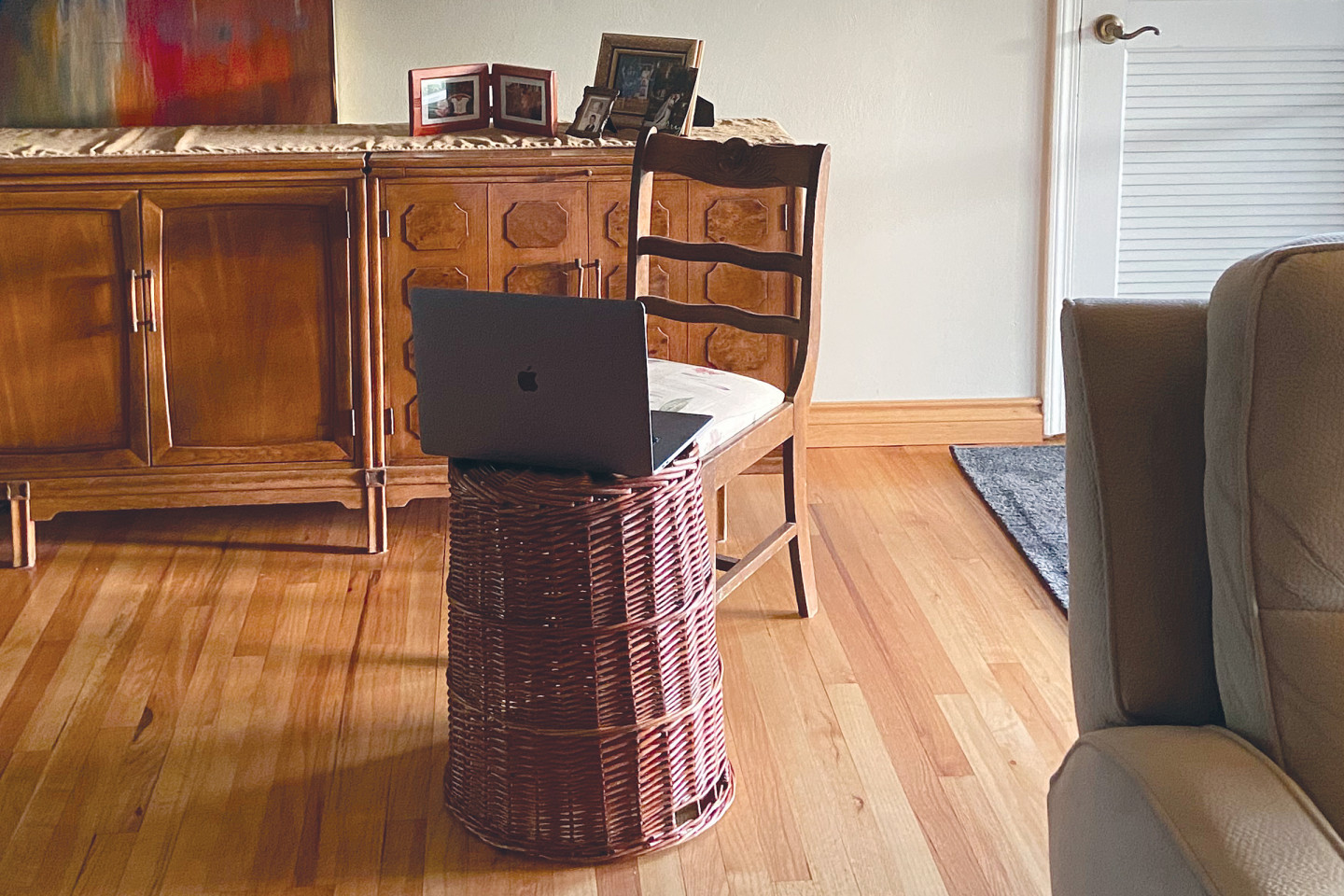 A laptop computer sits on an overturned laundry basket in a living room.