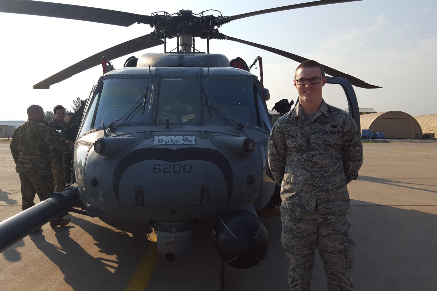 Russell Pliley stands next to a military helicopter.