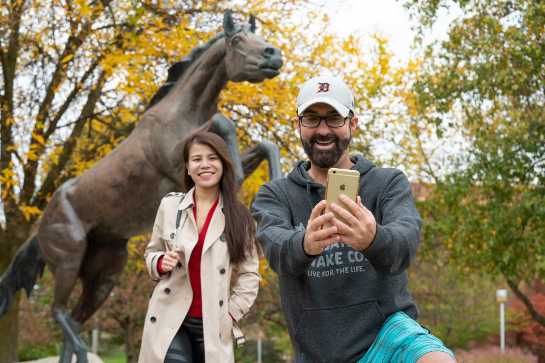 People take a selfie near the Bronco statue.