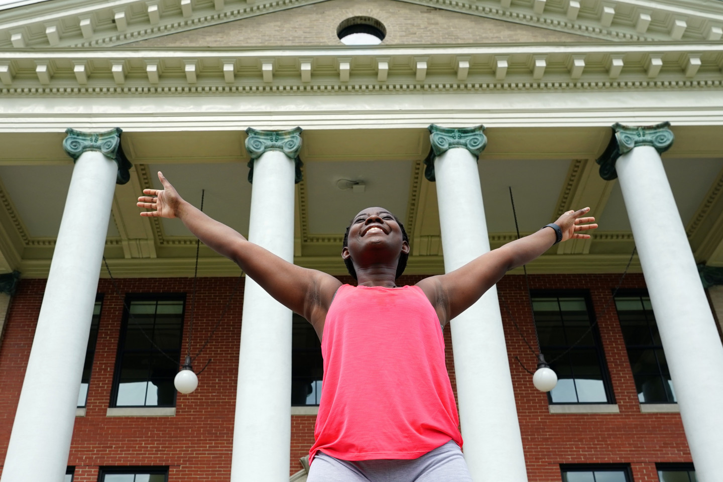 A student stands with her arms outstretched in front of Heritage Hall.