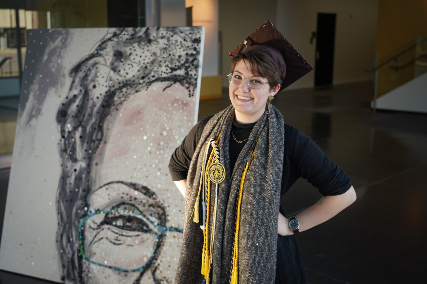 Rozlin Opolka stands in front of a painting she created of her grandmother.