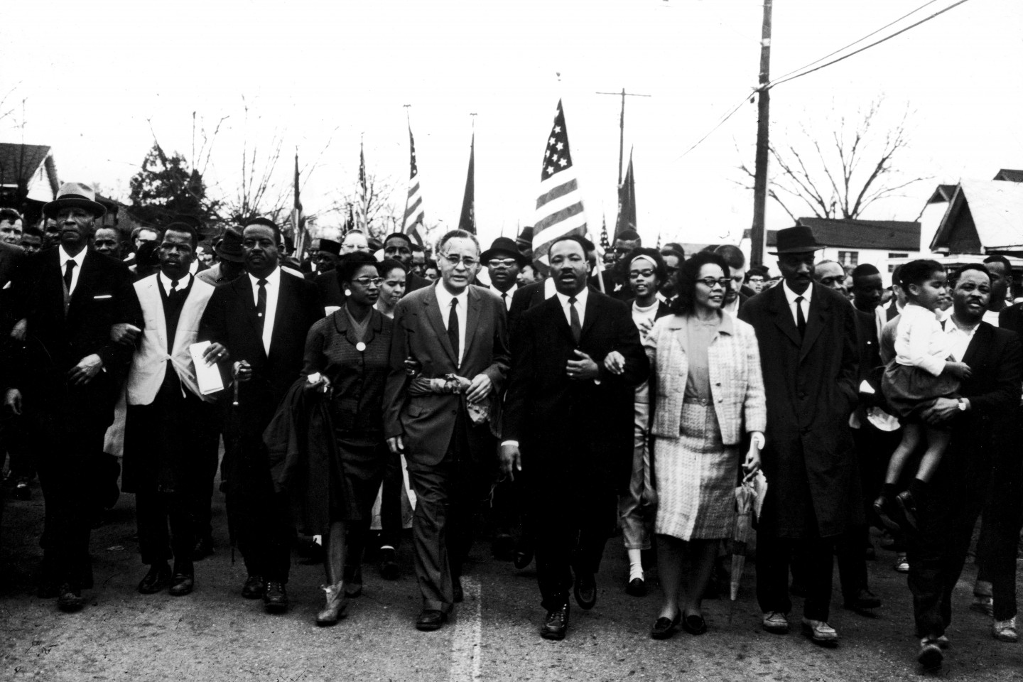 Martin Luther King Jr. marching with a crowd of people.