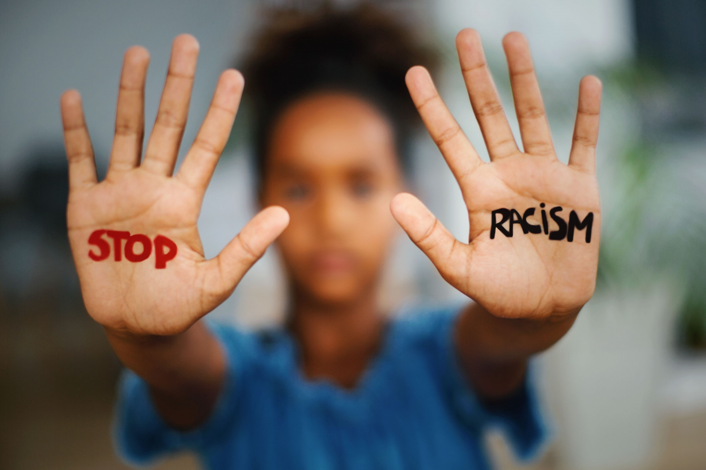"A person with ""stop racism"" written on their outstretched palms."