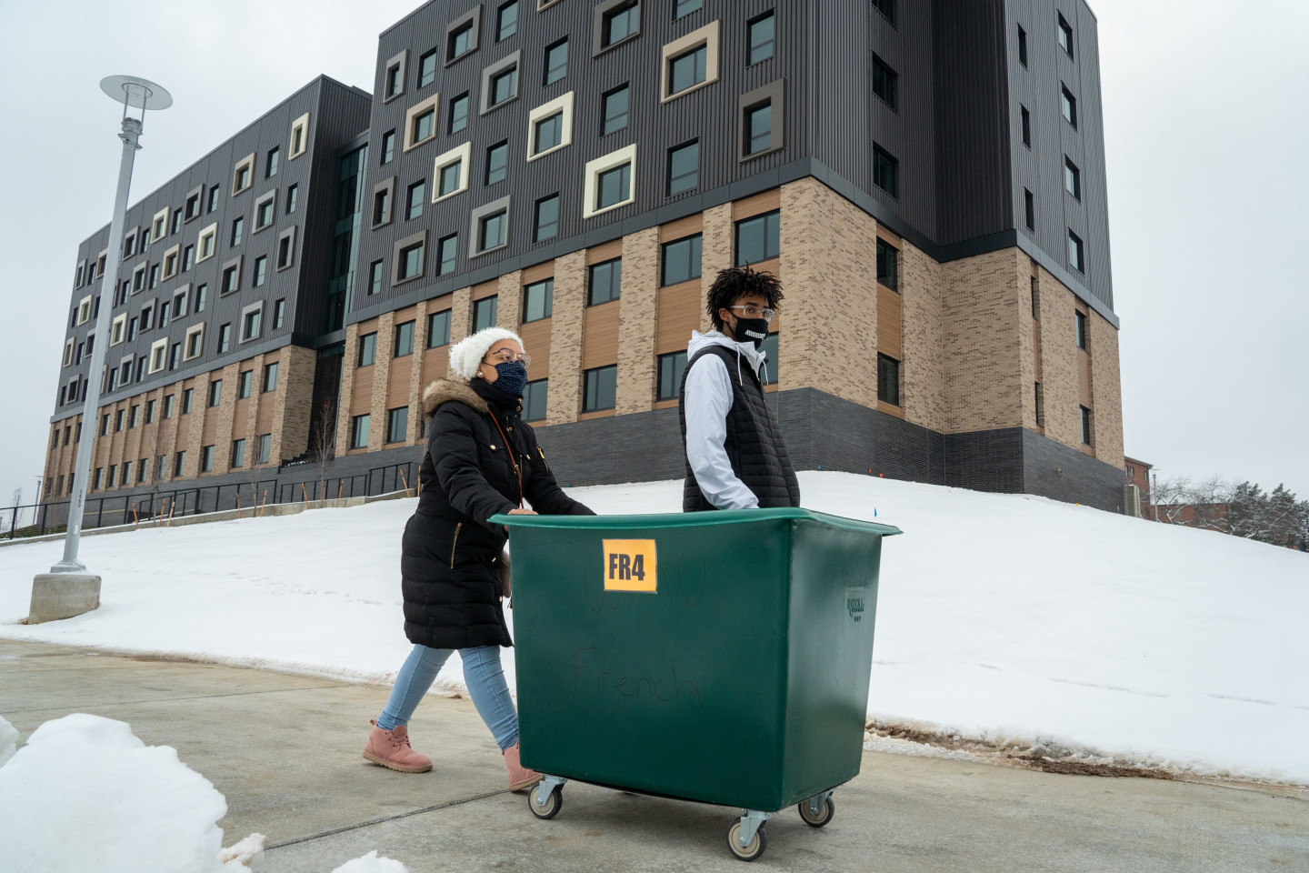 Students push a large bin down the sidewalk in front of Arcadia Flats.