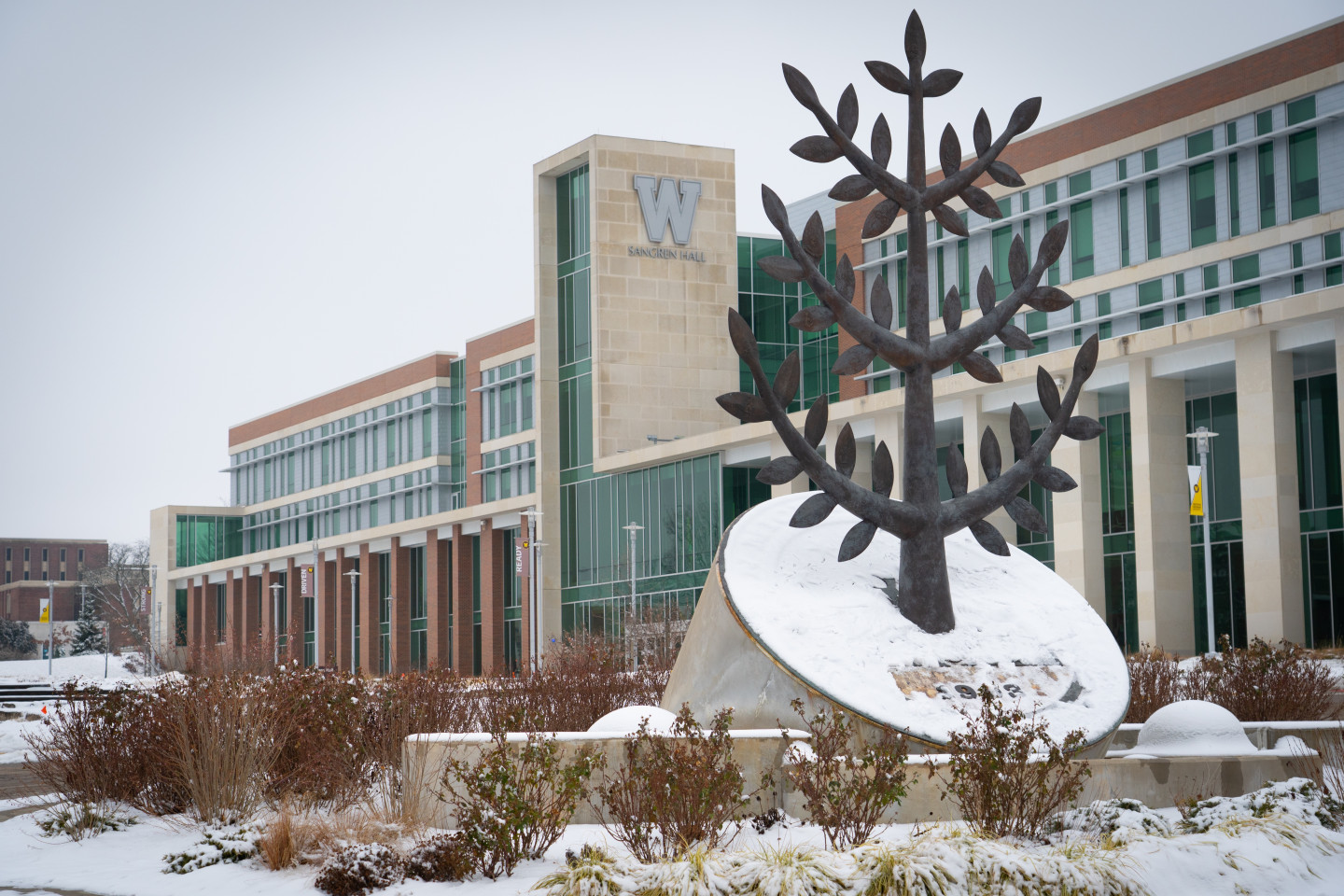 A winter photo of the WMU seal sculpture in front of Sangren Hall.