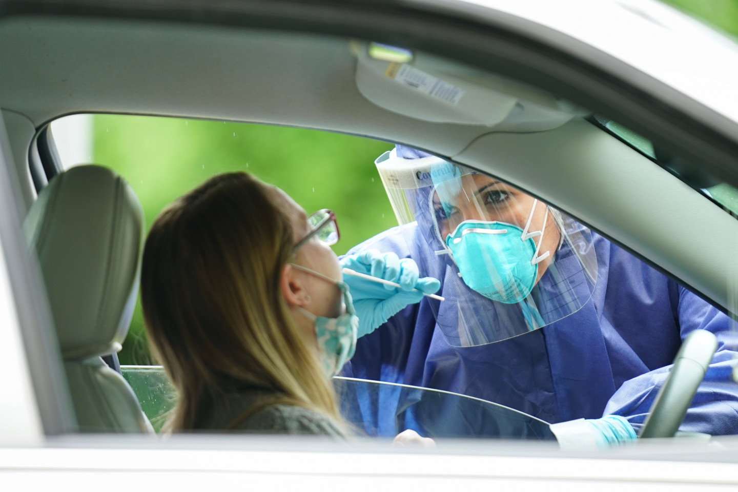 A medical professional administers a COVID-19 test to a driver through her car window.