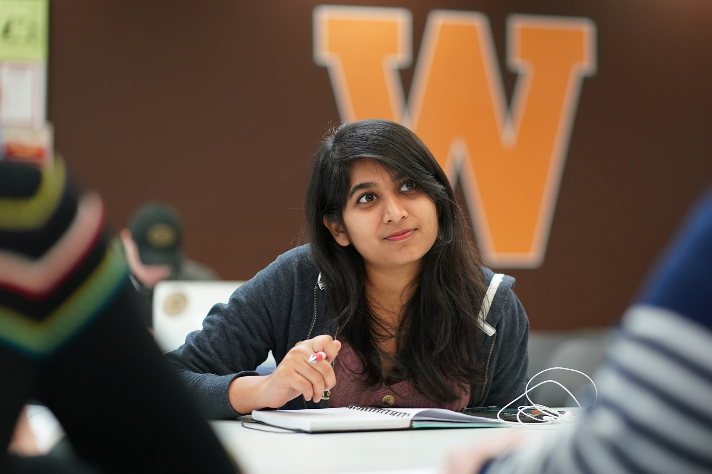 A student sits at a desk with a pen and notebook.