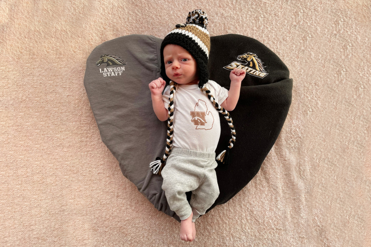 A baby lays on a heart made out of two t-shirts.