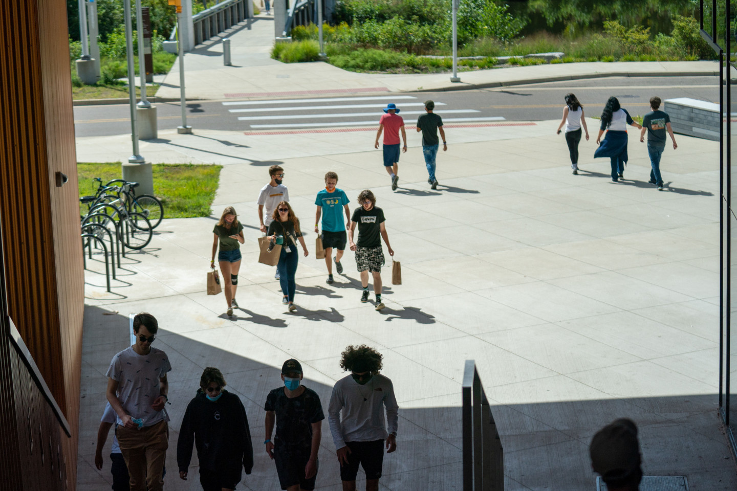 Students walking on a patio and up steps.