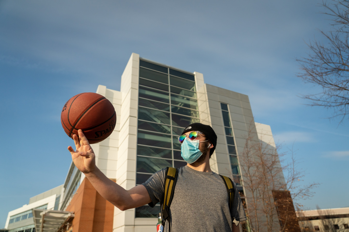 A student spins a basketball on his finger.