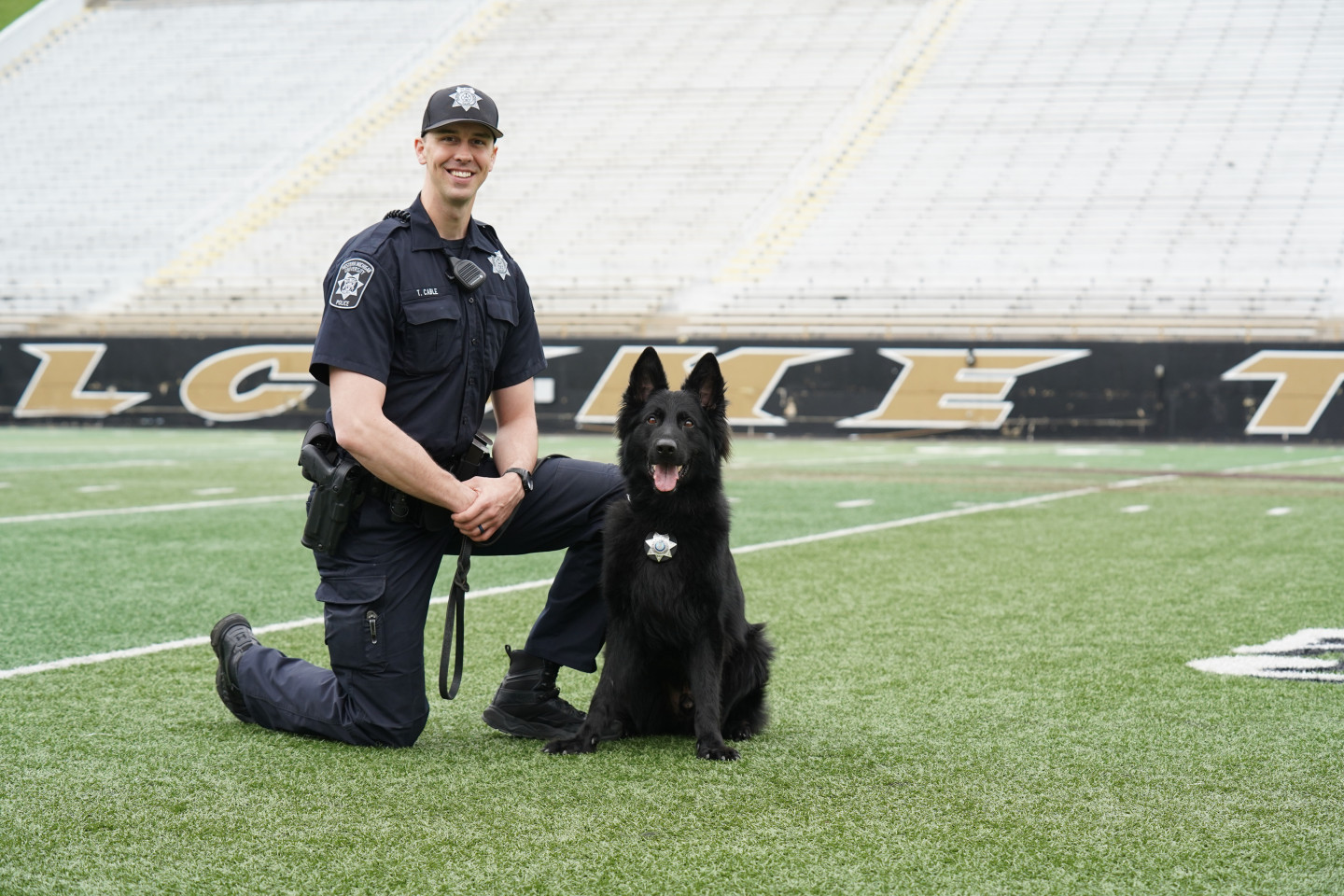 WMU officer Travis Cable poses next to his police K9 on the Waldo Stadium field.