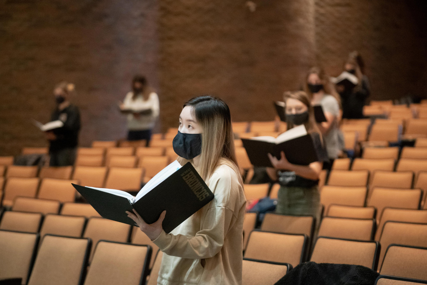 Choir students hold books of music and sing in an auditorium.