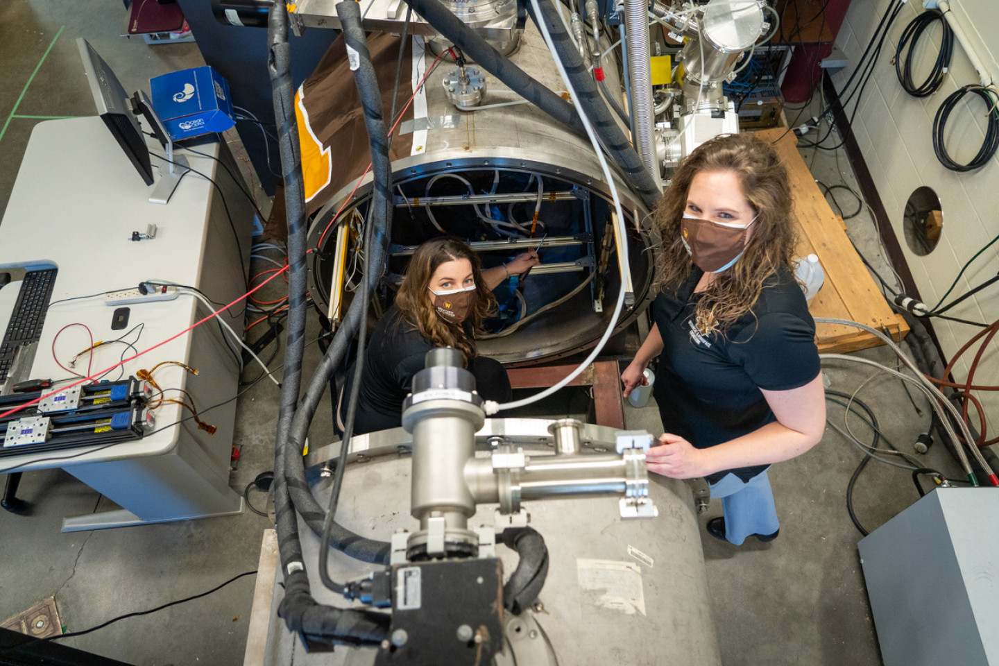Margaret Mooney and Dr. Kristina Lemmer pose for a picture inside an open vacuum chamber in an engineering laboratory.