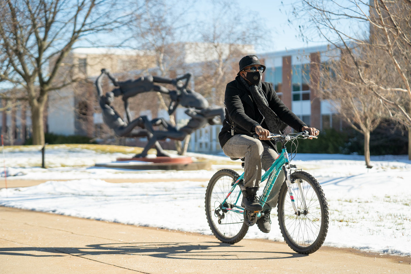 A masked student rides a bike on campus.