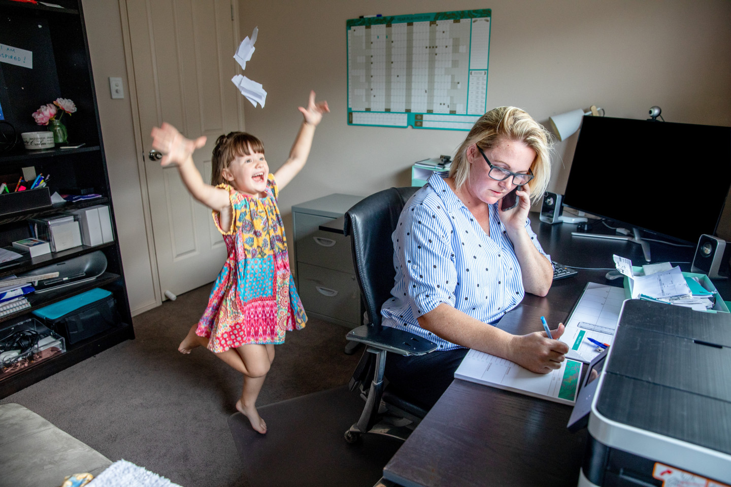 A mom talks on the phone while a child jumps and throws paper behind her.