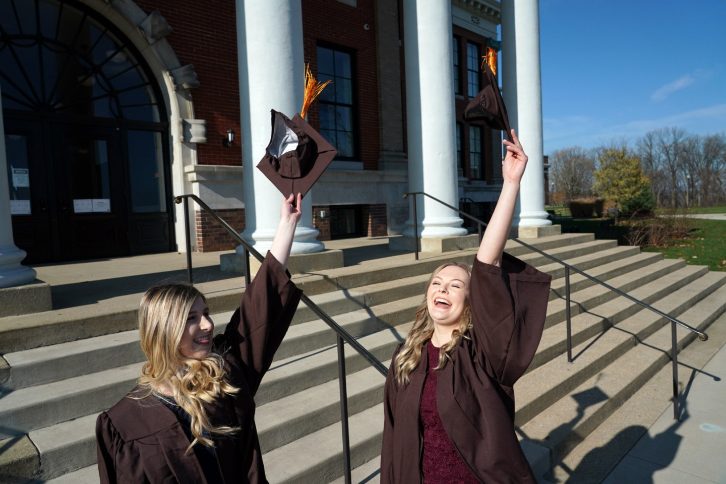 Two students in graduation attire celebrate on the steps of Heritage Hall.