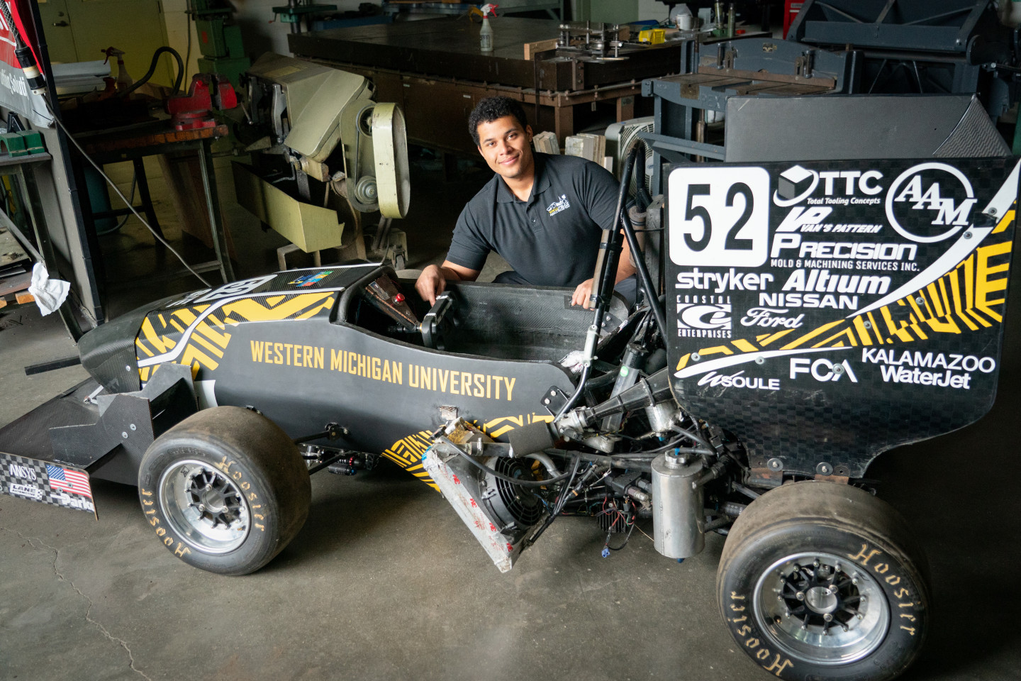 Nick Durham kneels next to a race car he helped build.