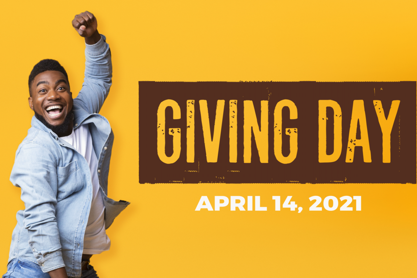 """A student jumps next to a """"Giving Day"""" logo."""