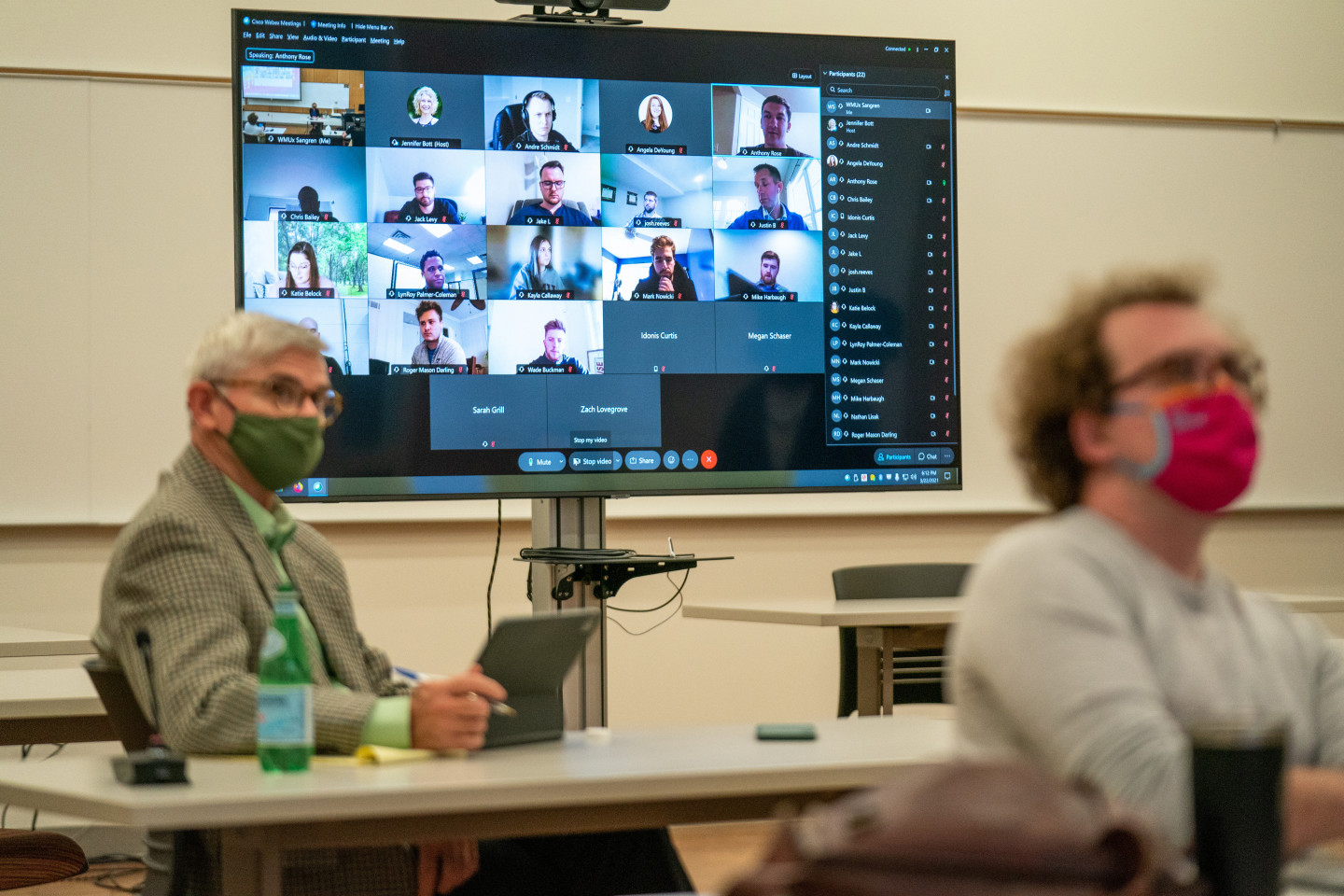 A large monitor with students in a video conference stands behind a class of students in desks.