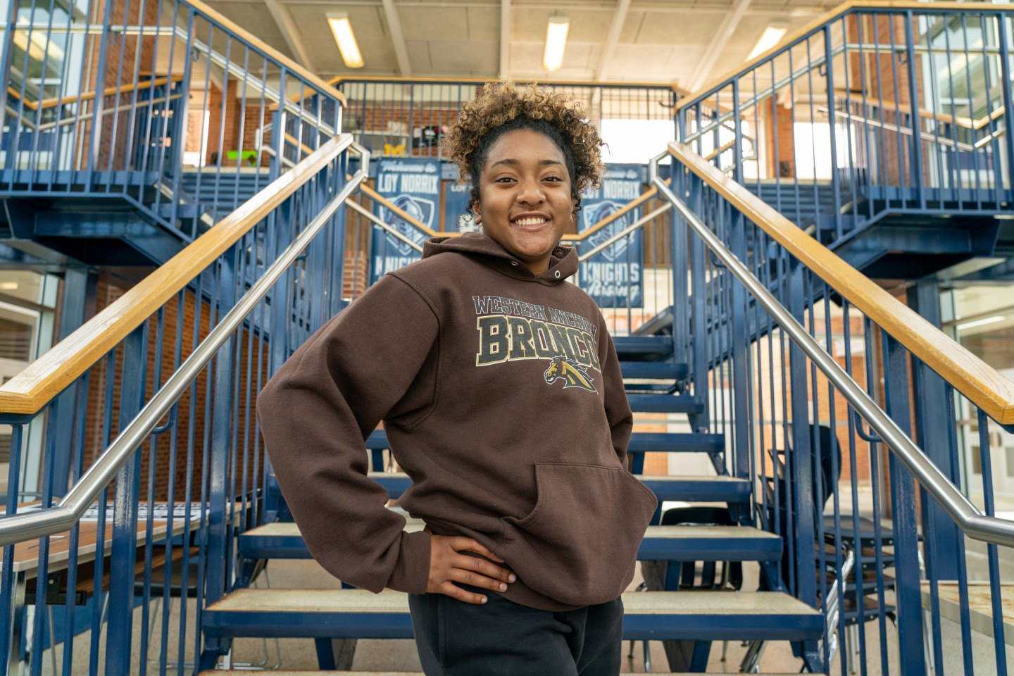 Sierra Ward stands at the bottom of a staircase.