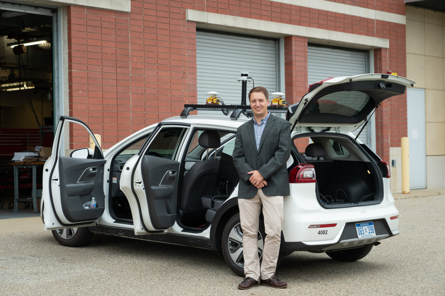 Dr. Zachary Asher stands next to a vehicle with its doors and trunk open.